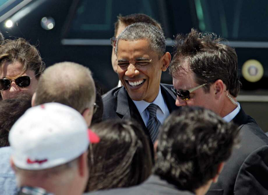 President Barack Obama greets supporters after arriving at Cleveland Hopkins International airport in Cleveland, Thursday, June 14, 2012, before attending a campaign event in the city. (AP Photo/Mark Duncan) Photo: Mark Duncan