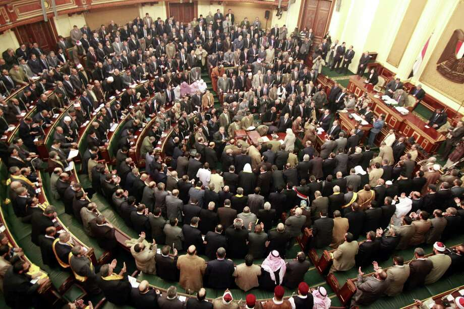 FILE - In this Monday, Jan. 23, 2012 file photo, members of parliament stand and pray for the souls of the victims who died during the uprising that ousted President Hosni Mubarak during the first Egyptian parliament session after the revolution, in Cairo, Egypt. Egypt's highest court ruled on Thursday, June 14, 2012 that the last prime minister to serve under Hosni Mubarak can stay in the presidential race and that a third of lawmakers in parliament were illegally elected, forcing a re-vote in a potential blow to Islamists who dominate the legislature.  (AP Photo/Asmaa Waguih,Pool, File) Photo: Asmaa Waguih