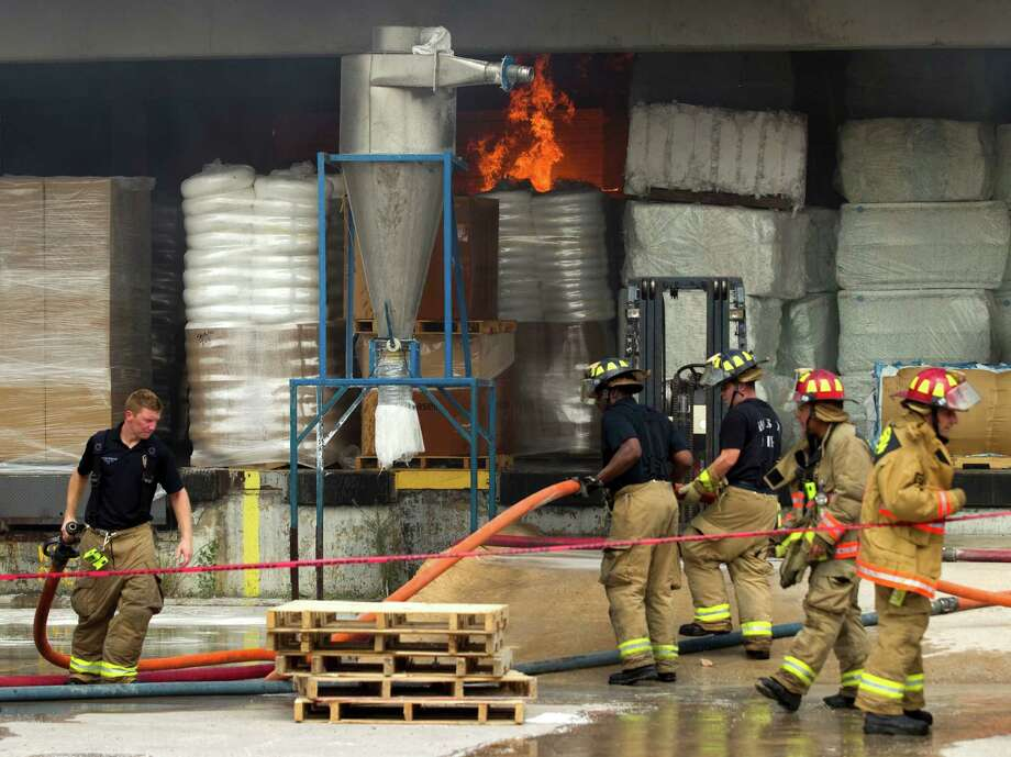 Houston firefighters battle a multiple alarm blaze at a warehouse which stores oil spill clean-up products Thursday, June 14, 2012, in Houston. One firefighter was treated at the scene for heat exhaustion. Photo: Brett Coomer, Houston Chronicle / © 2012 Houston Chronicle