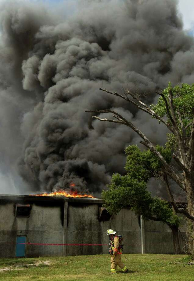 Smoke billows from a warehouse as Houston firefighters battle a multiple alarm blaze at a warehouse which stores oil spill clean-up products Thursday, June 14, 2012, in Houston. One firefighter was treated at the scene for heat exhaustion. Photo: Brett Coomer, Houston Chronicle / © 2012 Houston Chronicle