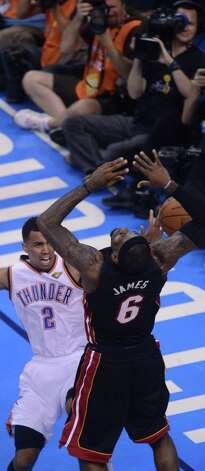 Thabo Sefolosha (L)  of the Oklahoma City Thunder and LeBron James (R) of the Miami Heat vie for a the ball during Game 2 of the NBA Finals at the Chesapeake Energy Arena in Oklahoma City, Oklahoma, June 14, 2012. The Oklahoma City Thunder face the Miami Heat in the best-of-seven series. AFP PHOTO / ROBYN BECKROBYN BECK/AFP/GettyImages Photo: ROBYN BECK, AFP/Getty Images / AFP