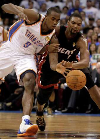 Oklahoma City Thunder power forward Serge Ibaka (9) from Republic of Congo and Miami Heat power forward Chris Bosh go after a loose ball during the first half at Game 2 of the NBA finals basketball series, Thursday, June 14, 2012, in Oklahoma City. (AP Photo/Jeff Roberson) Photo: Jeff Roberson, Associated Press / AP