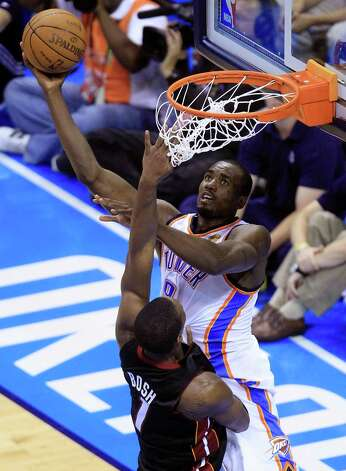 Oklahoma City Thunder power forward Serge Ibaka (9) from Republic of Congo shoots against Miami Heat power forward Chris Bosh during the first half at Game 2 of the NBA finals basketball series, Thursday, June 14, 2012, in Oklahoma City. (AP Photo/Sue Ogrocki) Photo: Sue Ogrocki, Associated Press / AP