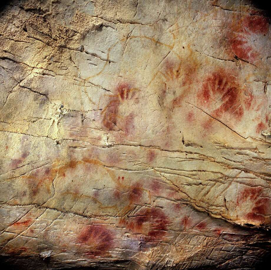 This undated handout photo provided by pedro suara/aaas shows detail of the 'Panel of Hands', El Castillo Cave showing red disks and hand stencils made by blowing or spitting paint onto the wall. A date from a disk shows the painting to be older than 40,800 years making it the oldest known cave art in Europe. The bison overlay the hands and are therefore painted later. New tests show that crude Spanish cave paintings of a red sphere and handprints are the oldest in the world, so ancient they may not have been by modern man. They might have even been made by the much-maligned Neanderthals, some scientists suggest but others disagree. (AP Photo/Pedro Saura, AAAS) Photo: Pedro Saura