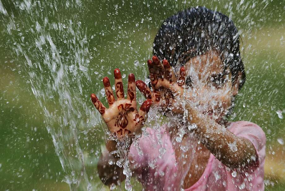 An Indian child, her palms decorated with henna, plays with water coming out from a broken pipe on a hot day in Allahabad, India, Thursday, June 14, 2012. Northern India has been sweltering under extreme heat. (AP Photo/Rajesh Kumar Singh) Photo: Rajesh Kumar Singh, Associated Press