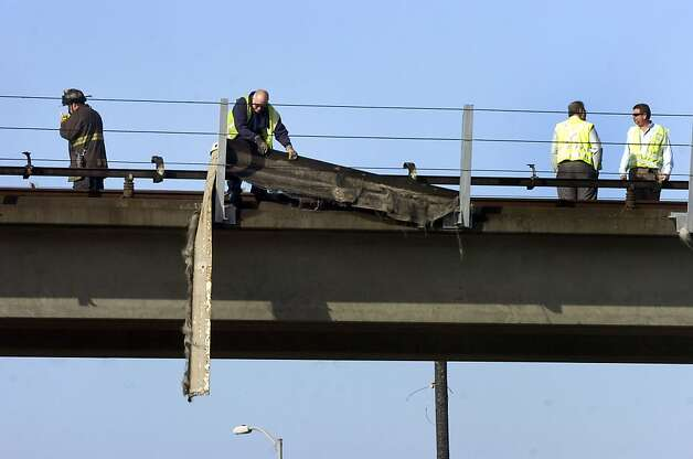 Workers check damage to the BART tracks near the West Oakland station after a fire below caused the shutdown of BART transbay service in Oakland, Calif., on Thursday, June 14, 2012. About 400,000 people take BART trains on a weekday, the transit agency said, but more commuters than usual were expected due to the opening round of the U.S. Open golf tournament and a San Francisco Giants afternoon baseball game.  (AP Photo/Bay Area News Group, Kristopher Skinner) Photo: Kristopher Skinner, Associated Press