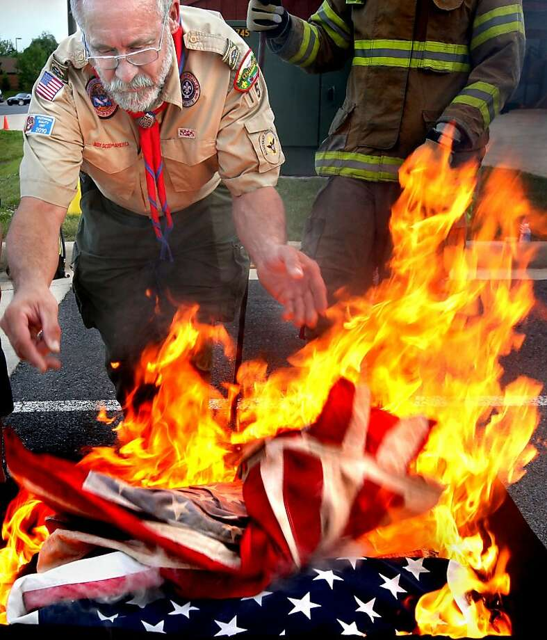 Boy Scout Troop 159 assistant scoutmaster Robert Hickel of Winchester, Va. adds an American flag to the flames during a Daughters of the American Revolution sponsored American flag retirement ceremony on Flag Day, Thursday, June 14, 2012 at the Shawnee Fire and Rescue Engine Company 4 in Winchester, Va.  (AP Photo/The Winchester Star, Jeff Taylor) Photo: Jeff Taylor, Associated Press