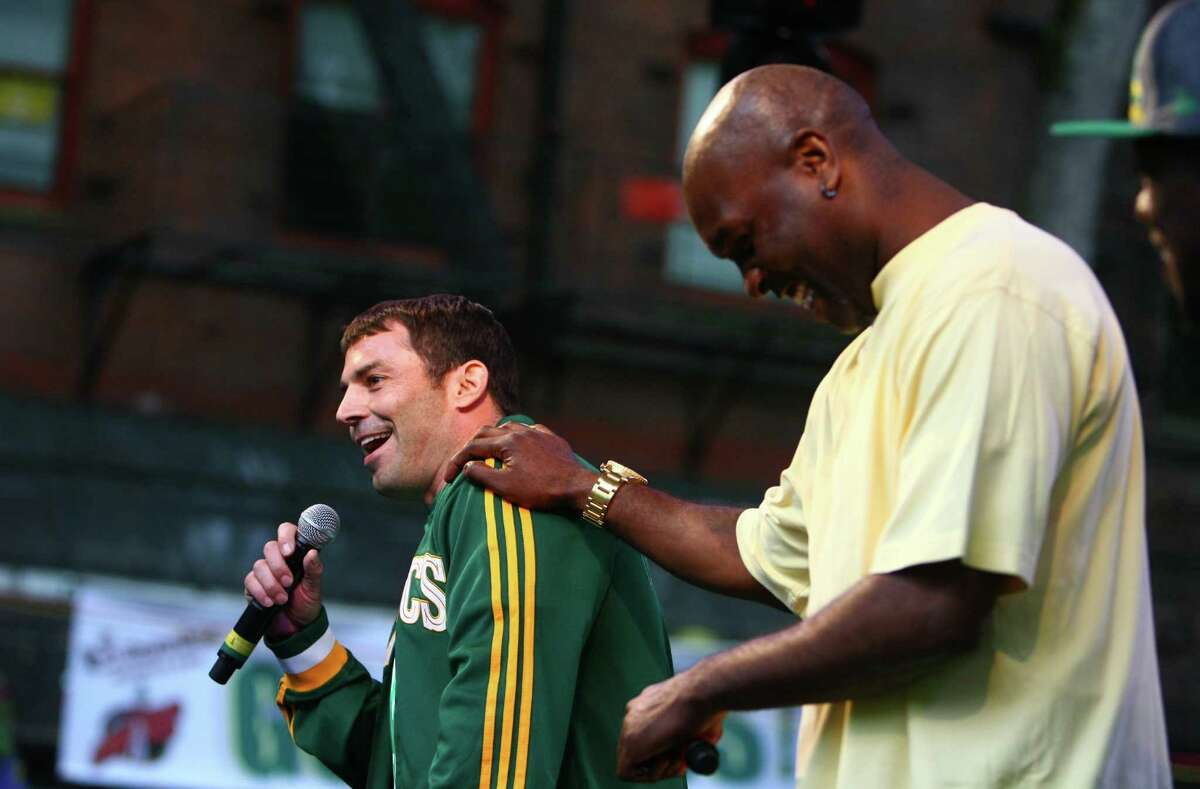 Investor Chris Hansen and former SuperSonic Gary Payton joke around on stage during a rally to bring back the Seattle SuperSonics. Thousands of people packed into Occidental Park to show support for bringing back the team.