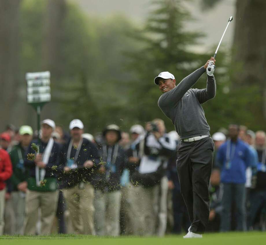 Tiger Woods hits a shot on the 11th hole during the first round of the U.S. Open Championship golf tournament Thursday, June 14, 2012, at The Olympic Club in San Francisco. (AP Photo/Charlie Riedel) Photo: Charlie Riedel