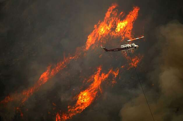 A helicopter flies through the Cache La Poudre Canyon as flames from a wildfire scorch the forest south of the river, near Fort Collins, Colo., Thursday afternoon, June 14, 2012. Flames crossed over the Poudre River causing a mandatory evacuation for residents of the Glacier View area. (AP Photo/The Denver Post, Karl Gehring) Photo: Karl Gehring, Associated Press