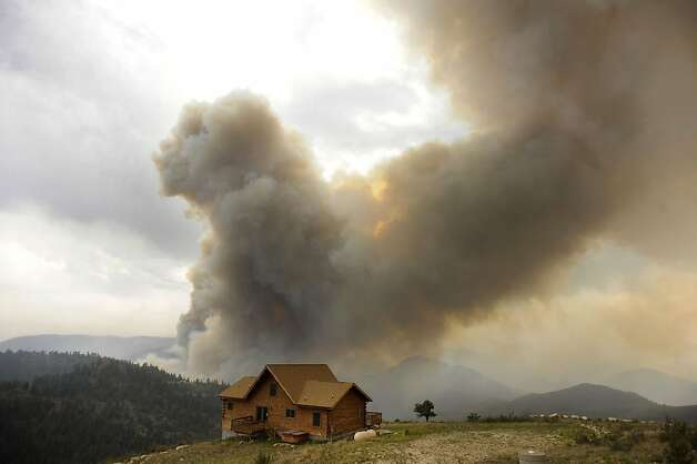 A plume of smoke rises from the High Park wildfire near Fort Collins, Colo., Thursday afternoon, June 14, 2012. Flames crossed over the Poudre River causing a mandatory evacuation for residents of the Glacier View area. (AP Photo/The Denver Post, Karl Gehring) Photo: Karl Gehring, Associated Press