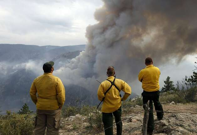Firefighters watch as flames leap hundreds of feet in the air as the High Park wildfire fire explodes on the south side of Poudre Canyon west of Fort Collins, Colo., on Thursday,  June 14, 2012. The wildfire started Saturday and has burned over 50,000 acres. (AP Photo/Ed Andrieski) Photo: Ed Andrieski, Associated Press