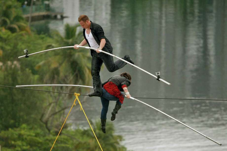 """FILE- In this June 4, 2011 file photo, high-wire acrobats Delilah Wallenda, right, lowers her head as her son Nik Wallenda, left, crosses over her during their high-wire act where the two simultaneously walked across a 300-foot-long wire suspended 100 feet in the air between two towers of the Conrad Condado Plaza Hotel in San Juan, Puerto Rico. They were honoring Nik's great-grandfather, Karl Wallenda, who tried to perform the same feat in 1978 but fell to his death at age 73. On Friday, June 15, 2012, Karl's great grandson, Nick Wallenda, will attempt a high wire walk over Niagara Falls on live television, hoping to write his famous family's name into the 153-year-old legend of daredevils who've """"conquered"""" the natural wonder. Photo: Ricardo Arduengo"""
