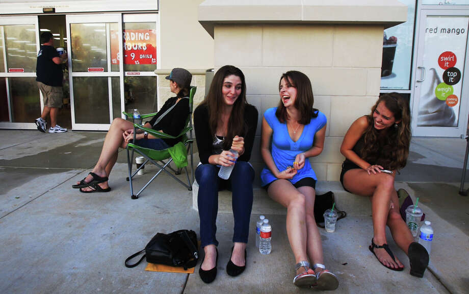 Customers,  from left to right, Kim Harvey, Nicole Mignano, Victoria Dobbie and Katie  Hauser wait Friday morning for the grand opening of Trader Joe's inside the  Woodlands Crossing Shopping Center in The Woodlands. Photo: Cody Duty, Houston Chronicle