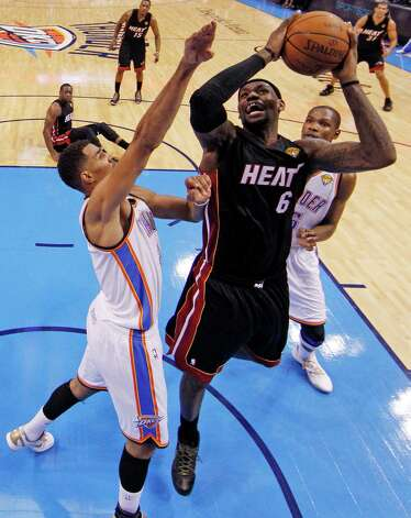 Miami Heat small forward LeBron James  (6) shoots as Oklahoma City Thunder shooting guard Thabo Sefolosha (2) of Switzerland and small forward Kevin Durant defend during the second half at Game 2 of the NBA finals basketball series, Thursday, June 14, 2012, in Oklahoma City. (AP Photo/Jim Young, Pool) Photo: Jim Young, Associated Press / Reuters Pool