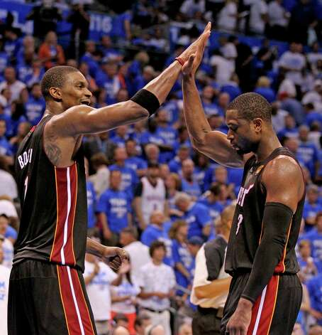 The Miami Heat's Chris Bosh, left, and Dwyane Wade high-five after a 100-96 win over the Oklahoma City Thunder in Game 2 of the NBA Finals on Thursday, June 14, 2012, at Chesapeake Energy Arena in Oklahoma City, Oklahoma. The Heat's win evens the series, 1-1. (Al Diaz/Miami Herald/MCT) Photo: Al Diaz, McClatchy-Tribune News Service / Miami Herald