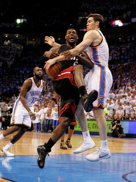 The Miami Heat's LeBron James is fouled by the Oklahoma City Thunder's Nick Collison, right, in the