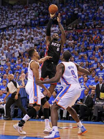 The Miami Heat's LeBron James shoots a 3-pointer over the Oklahoma City Thunder's Thabo Sefolosha and Serge Ibaka in the fourth quarter in Game 2 of the NBA Finals on Thursday, June 14, 2012, at Chesapeake Energy Arena in Oklahoma City, Oklahoma. The Heat won, 100-96,to even the series, 1-1. (Al Diaz/Miami Herald/MCT) Photo: Al Diaz, McClatchy-Tribune News Service / Miami Herald