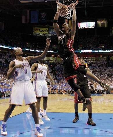 Miami Heat power forward Chris Bosh  dunks as Oklahoma City Thunder power forward Serge Ibaka (9) from Republic of Congo looks on during the second half at Game 2 of the NBA finals basketball series, Thursday, June 14, 2012, in Oklahoma City. The Heat won 100-96. (AP Photo/Jeff Roberson) Photo: Jeff Roberson, Associated Press / AP