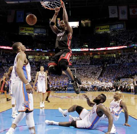 Miami Heat power forward Chris Bosh  dunks as Oklahoma City Thunder point guard Russell Westbrook (0), left, looks on during the second half at Game 2 of the NBA finals basketball series, Thursday, June 14, 2012, in Oklahoma City. Thunder guard James Harden (13) and point guard Derek Fisher (37) watch from the floor. The Heat won 100-96. (AP Photo/Jeff Roberson) Photo: Jeff Roberson, Associated Press / AP