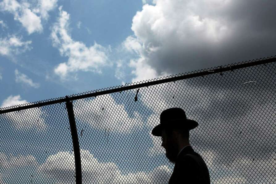 NEW YORK, NY - JUNE 14: A member of the Jewish Orthodox community walks down a street in a Brooklyn