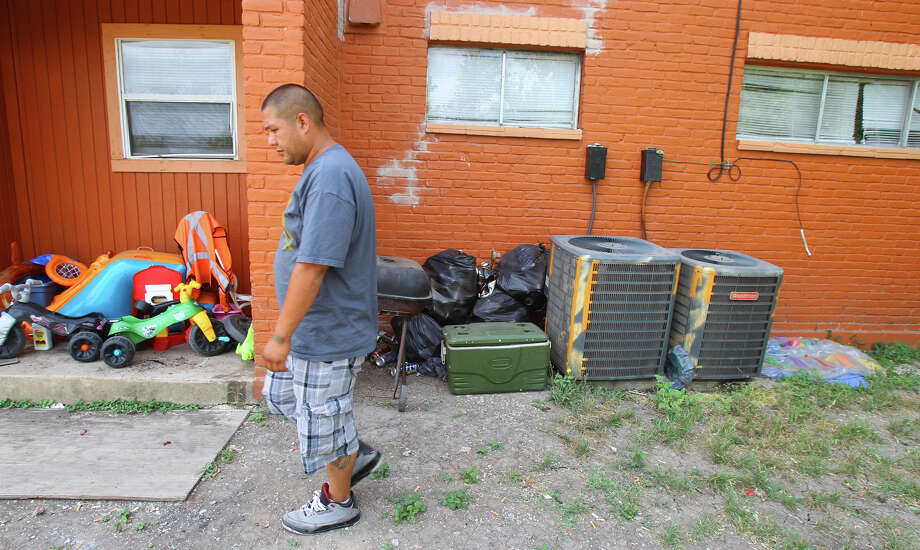 Jose Garcia,30, walks past an area at an apartment complex on the 3700 block of East Commerce street where his friend Daniel Goodwin got into an argument Thursday June 14, 2012. Daniel Goodwin, 41, and his son Darrius Goodwin,20, reportedly took the argument inside of the apartment where Darrius Goodwin is suspected of fatally shooting father. Darrius Goodwin has been arrested and charged with murder. Photo: SAN ANTONIO EXPRESS-NEWS