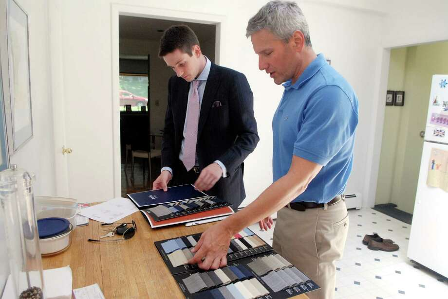 Leonard Logsdale, working with Carnaby Custom tailoring,helps Mike Guarnieri, an executive at GE, pick a fabric for a sports coat at Mike's Stamford, Conn. home on Friday June 15, 2012. The business is based in New York, but caters to clients in the Fairfield County area Photo: Dru Nadler / Stamford Advocate Freelance