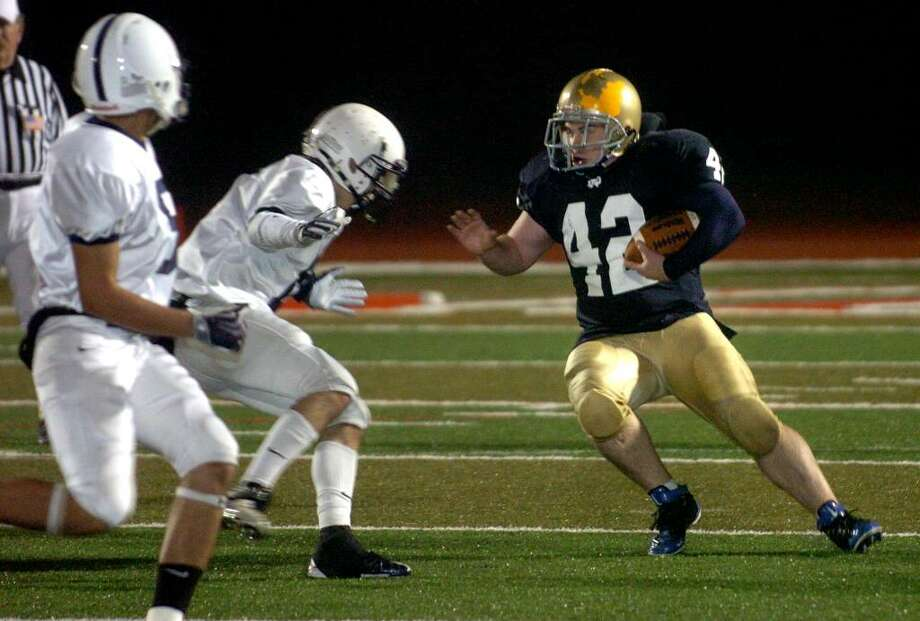 Notre Dame of Fairfield's #42 Brody Brandstatter, right, looks to avoid Immaculate players, during football action at Sacred Heart University in Fairfield, Conn. on Wednesday Nov. 25, 2009. Photo: Christian Abraham / Connecticut Post