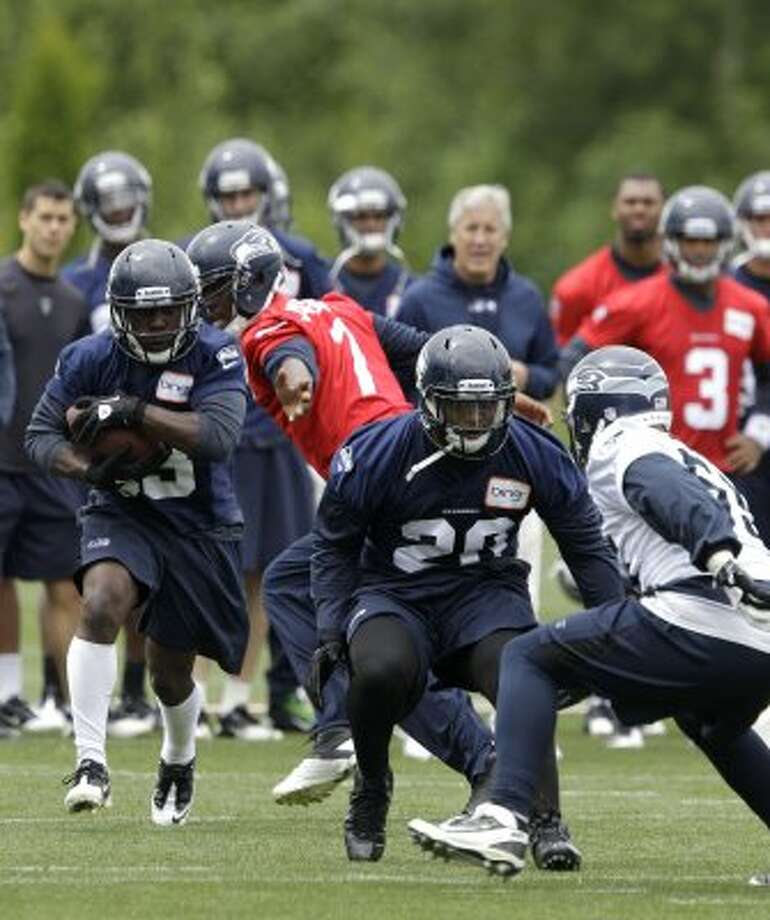 Seattle Seahawks' Leon Washington, left, takes a handoff from quarterback Tavaris Jackson, second from left, as Kregg Lupkin (20) squares off to block Heath Farwell, right, during practice Thursday, June 14, 2012, in Renton. (Ted S. Warren / Associated Press)