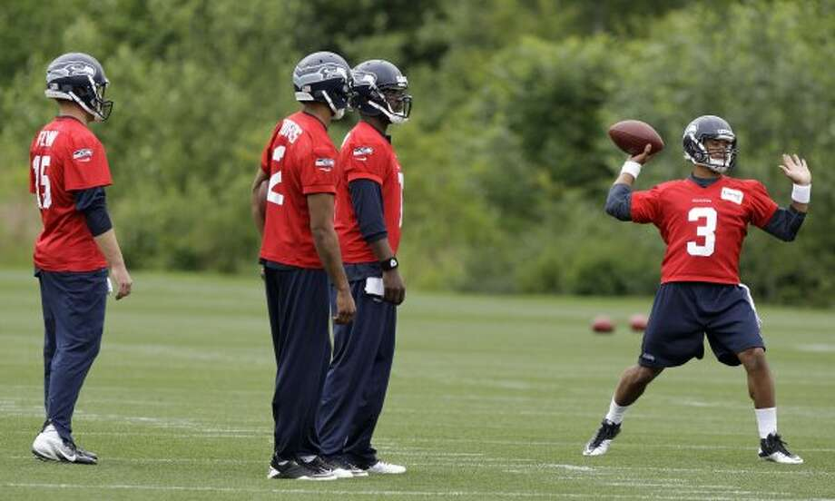 Seattle Seahawks quarterback Russell Wilson, right, passes as fellow quarterbacks, from left, Matt Flynn, Josh Portis, and Tavaris Jackson, look on, during practice Thursday, June 14, 2012, in Renton. (Ted S. Warren / Associated Press)