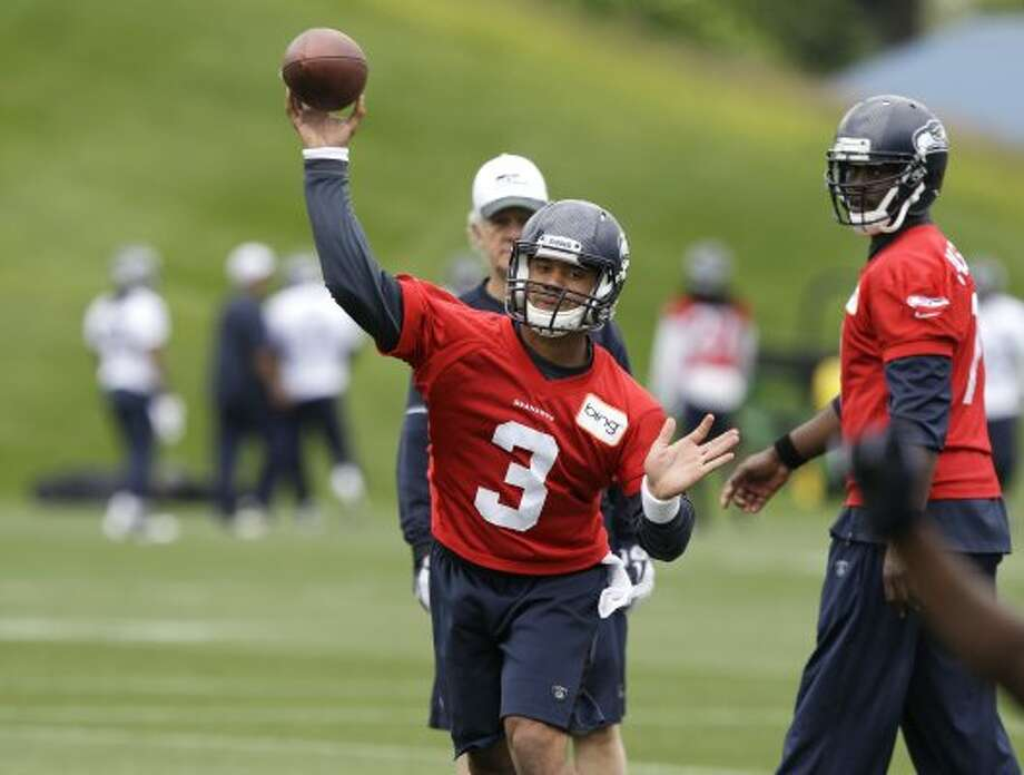 Seattle Seahawks quarterback Russell Wilson (3) passes as quarterback Tavaris Jackson looks on at right, during practice Thursday, June 14, 2012, in Renton. (Ted S. Warren / Associated Press)