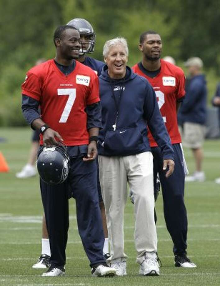 Seattle Seahawks quarterback Tavaris Jackson (7) chats with head coach Pete Carroll, center, as they stand with quarterback Josh Portis, right, during practice Thursday, June 14, 2012, in Renton. (Ted S. Warren / Associated Press)