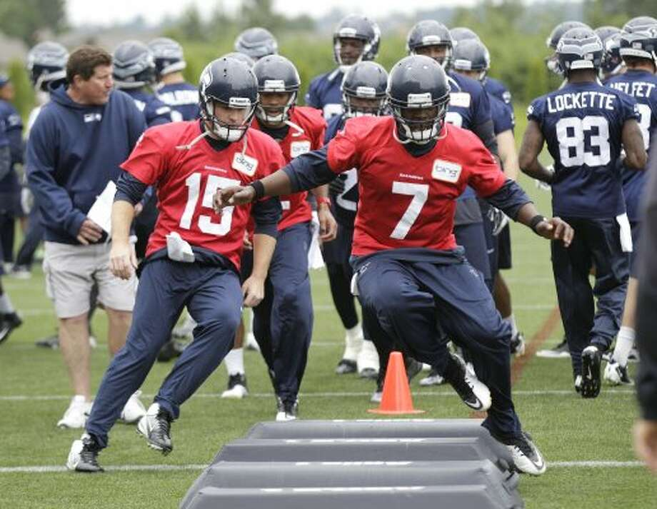 Seattle Seahawks quarterback Tavaris Jackson (7) leads quarterback Matt Flynn (15) and other players through an agility drill during practice Thursday, June 14, 2012, in Renton. (Ted S. Warren / Associated Press)