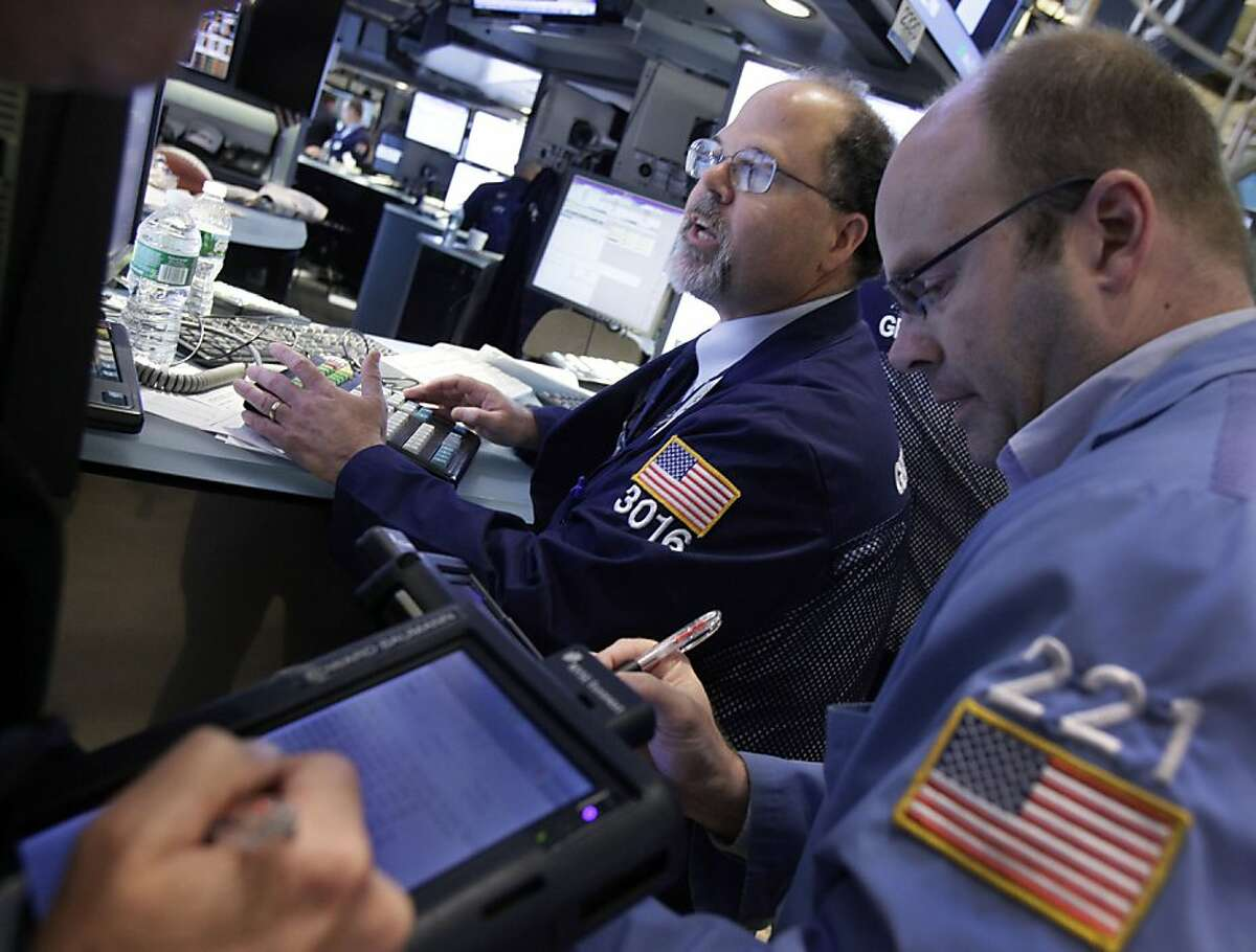 Specialist Douglas Johnson, center, works at his post on the floor of the New York Stock Exchange Friday, June 15, 2012. U.S. stocks are opening higher as investors anticipate action by central banks to head off a deeper European debt crisis. (AP Photo/Richard Drew)