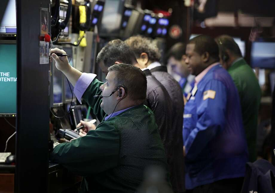 Traders work on the floor of the New York Stock Exchange Friday, June 15, 2012. U.S. stocks are opening higher as investors anticipate action by central banks to head off a deeper European debt crisis. (AP Photo/Richard Drew) Photo: Richard Drew, Associated Press