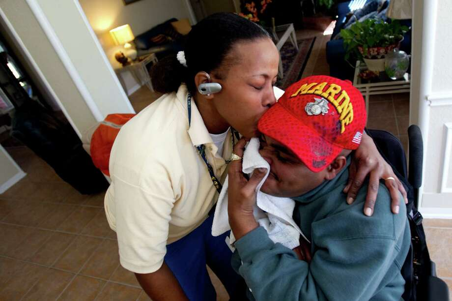Leland Spencer, 39, tries to hide with a towel as his twin sister Lianne Spencer, 39, kisses his face at their mother's home in northeast Houston Friday, Nov. 5, 2010. While stationed with the U.S. Marine Corps in Okinawa, Japan, Leland contracted Encephalitis Type B, a neurologic infection spread by mosquitoes which left him wheelchair bound. Spencer had $200,000 stolen by a VA-approved guardian and attorney named Joe Phillips, who is now being prosecuted for stealing more than $2 million from Texas veterans, most of whom lived in Houston. (Johnny Hanson / Houston Chronicle) Photo: Johnny Hanson / Houston Chronicle