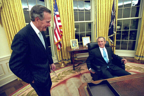 **FILE**--President George W. Bush talks to his father, former President Bush as he sits at his desk in the Oval Office in this file photo for the first time on Inaugural Day, Jan. 20, 2001. In many ways, large and small, George W. Bush's presidency has become a mirror image of his fathers. (AP Photo/Eric Draper, White House, File)