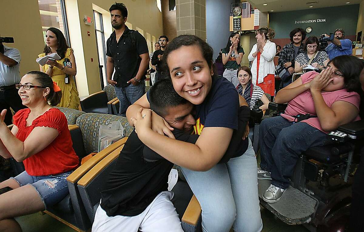 Maria Ibarra,19, originally from Durango Mexico and Candido Renteria, 24, of Monterrey Nuevo Leon, hug with joy after President Obama announced he would ease enforcement of immigration laws, Friday, June 15, 2012 in Edinburg, Texas. Many students gathered at the student union at the UTPA Campus in Edinburg to watch the annoucement. (AP Photo/The Monitor, Delcia Lopez) MAGS OUT; TV OUT