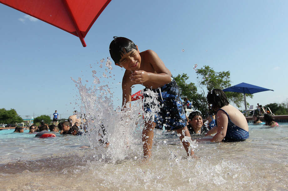 Anthony Aragon, 6, plays near a fountain at the Heritage swimming pool on Wednesday, June 13, 2012. Heritage has only been open for its second season but has already proven a hit with area residents. San Antonians flocked to the city pools to cool off from the summer heat. The city's Park and Recreation department will officially kick off summer hours on Saturday when they will operate the pools six days a week except Mondays and operate from 1to 7 p.m. Photo: Kin Man Hui, San Antonio Express-News / © 2012 San Antonio Express-News