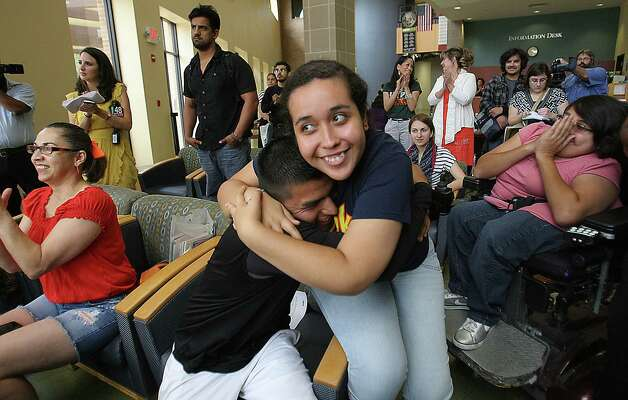 Maria Ibarra,19, originally from Durango Mexico and Candido Renteria, 24, of Monterrey Nuevo Leon, hug with joy after President Obama announced he would ease enforcement of immigration laws, Friday, June 15, 2012 in Edinburg, Texas. Many students gathered at the student union at the UTPA Campus in Edinburg to watch the annoucement.  (AP Photo/The Monitor, Delcia Lopez)  MAGS OUT; TV OUT Photo: AP