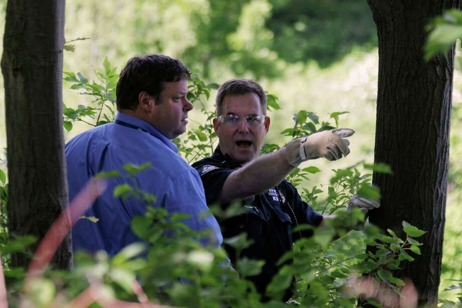 Law enforcement officers search near the home of Dr. Timothy Jorden in Hamburg, N.Y., Thursday, June 14, 2012. Jorden is sought in connection with the hospital shooting death of his ex-girlfriend at Erie County Medical Center in Buffalo, N.Y. on Wednesday.  (AP Photo/David Duprey) Photo: David Duprey
