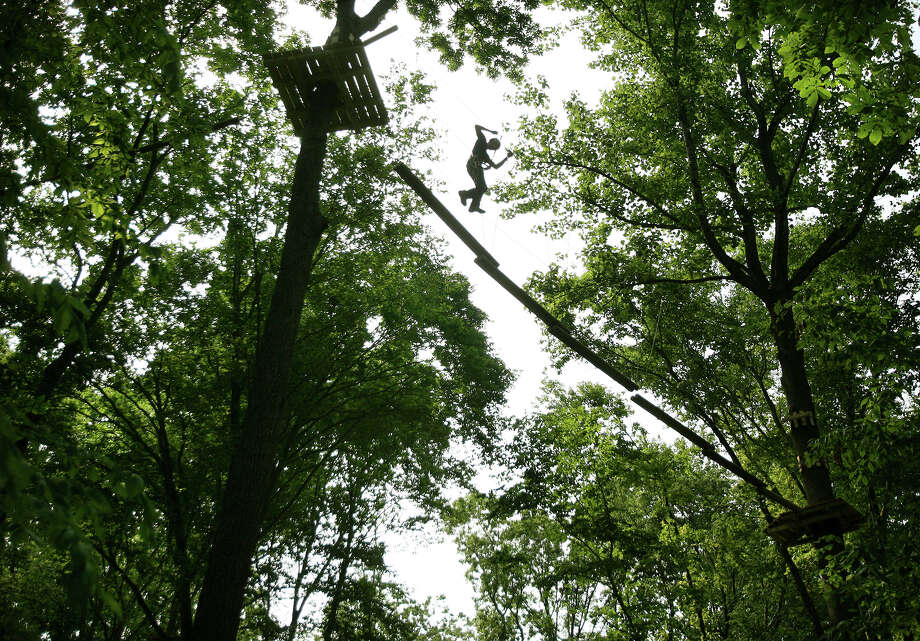 Chirs Nischan of Fairfield works high up in the tree canopy on the most challenging Commando course at the new Adventure Park at the Discovery Museum in Bridgeport on Monday, June 11, 2012. Photo: Brian A. Pounds / Connecticut Post
