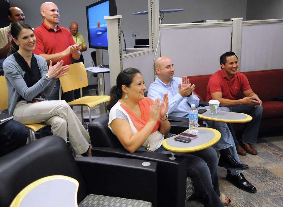 USAA has relaxed its dress code to allow employees, such as those shown in this 2012 photo, to don shorts as long as they don't have face-to-face contact with customers or visitors. Under the revised code, workers also can sport sandals with a heal strap and tennis shoes. (Express-News file photo) Photo: Billy Calzada, San Antonio Express-News / © 2012 San Antonio Express-News
