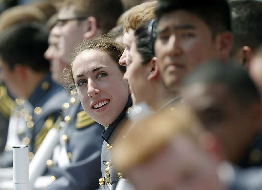 In this Saturday, May 26, 2012 photo, Kaitlyn Kelly reacts after a graduation and commissioning ceremony at the U.S. Military Academy in West Point, N.Y. At West Point, the alumni gay advocacy group Knights Out was able to hold the first installment in March of what is intended to be an annual dinner in recognition of gay and lesbian graduates and cadets. Kelly was among the dozens of cadets who attended the privately sponsored dinner. The 22-year-old Chicago resident was finally able to openly introduce her civilian girlfriend at an event marking 100 days before graduation. (AP Photo/Mike Groll) Photo: Mike Groll, Associated Press