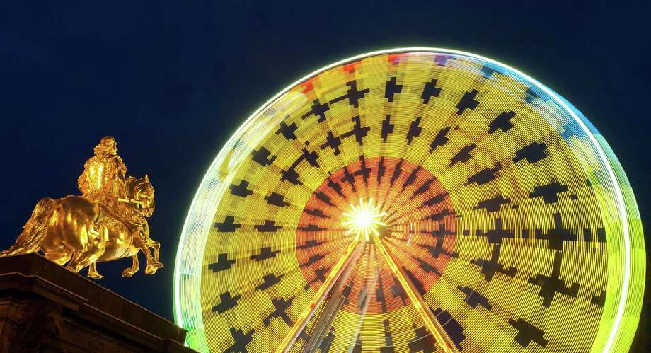 A colorful wheel spins at the Christmas market behind the Golden Rider statue in Dresden, Germany during the Christmas Market. Photo: ROBERT MICHAEL, AFP/Getty Images / 2011 AFP