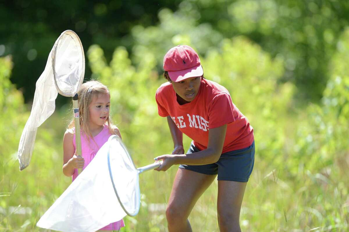 Second-grader Emily Bond, left, is assisted by camp counselor Tracie Harris in catching dragonflies for study as part of Ecology Day Camp at the University of Mississippi Biological Field Station in Abbeville, Miss.