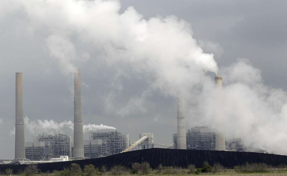 In this Wednesday, March 16, 2011 file photo, exhaust rises from smokestacks in front of piles of coal at NRG Energy's W.A. Parish Electric Generating Station in Thompsons, Texas. Risking an election-year backlash from Republicans, the Obama administration is proposing new air quality standards to lower the amount of soot that can be released into the air. The move by the Environmental Protection Agency on Friday, June 15, 2012 won immediate support from environmental groups and public health advocates, who said the EPA was protecting millions of Americans at risk of asthma attacks, lung cancer, heart disease and premature death. But congressional Republicans and industry officials called the rules overly strict and said they could hurt economic growth and cause job losses in areas where pollution levels are determined to be too high. (AP Photo/David J. Phillip) Photo: David J. Phillip, Associated Press