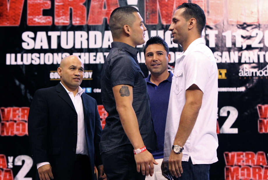 "Boxers Brian Vera (left, foreground, tattoo on arm) and Sergio Mora (white shirt, right) stare each other down at a press conference Friday June 15, 2012 at the Alamodome. The boxers will face each other for the NABO middleweight title on August 11, 2012 at the Alamodome's Illusions Theater. In the background are retired boxers ""Jesse"" James Leija (left, wearing blazer) and Oscar De La Hoya (wearing polo shirt). Photo: John Davenport, San Antonio Express-News / SAN ANTONIO EXPRESS-NEWS"