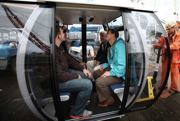 Seattle Great Wheel owner Hal Griffith, center rear, Brian Bilanski, right, and Hunter Herrin, left, try out the seats in a gondola about to be attached to the Seattle Great Wheel on Tuesday, June 5, 2012. Photo: JOSHUA TRUJILLO / SEATTLEPI.COM