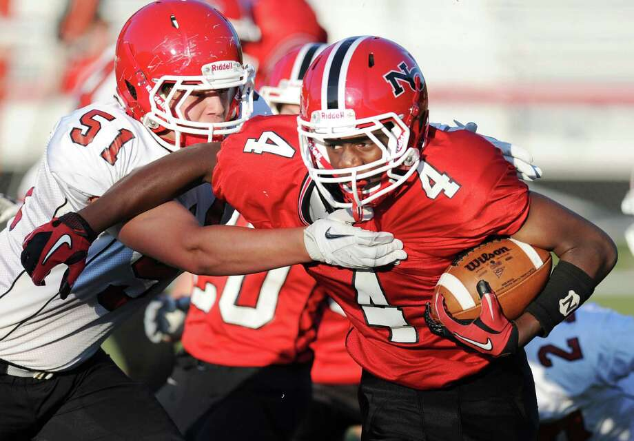 New Canaan High School running back Chris Andrews # 4 of the red team gets past Beau Santero # 51 of the white team during the 5th annual New Canaan Football Brian Wilderman Memorial Red & White game at New Canaan High School, Friday, June 15, 2012. Photo: Bob Luckey / Greenwich Time